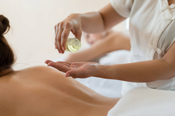 Masajista Vierta el aceite en la mano y joven mujer asiática relajante recibir masaje de espalda en el salón de spa - foto de stock