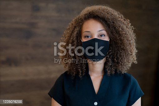 Portrait of an African American masseuse working at a spa and wearing a facemask to avoid the coronavirus – pandemic lifestyle concepts