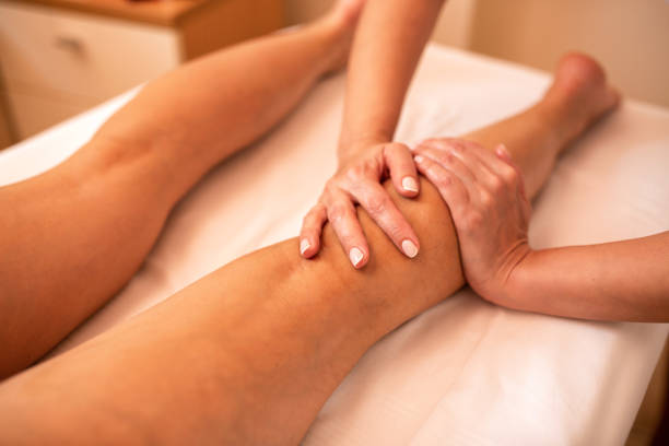 Masseuse working on a calf muscle area stock photo