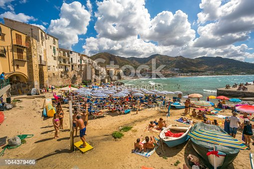 Cefalu, Sicily, Italy - August 13, 2017: Cefalu  view showing people relaxing on the beach side and swimming in the sea in Massimo Villas, umbrellas, boats, rock mountains and buildings can be seen on the background