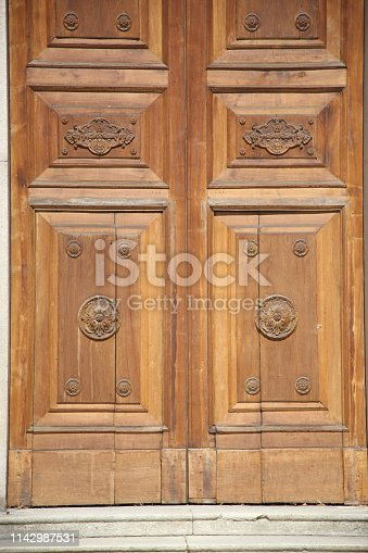 Massive doors of valuable wood in the Catholic church. Lecce, Italy