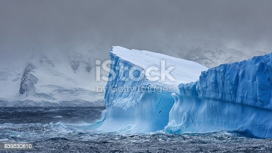 Massive Iceberg floating in the Southern Ocean in Antarctica with snow covered mountains in the background