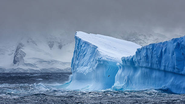Massive Iceberg floating in Antarctica Massive Iceberg floating in the Southern Ocean in Antarctica with snow covered mountains in the background ice floe stock pictures, royalty-free photos & images
