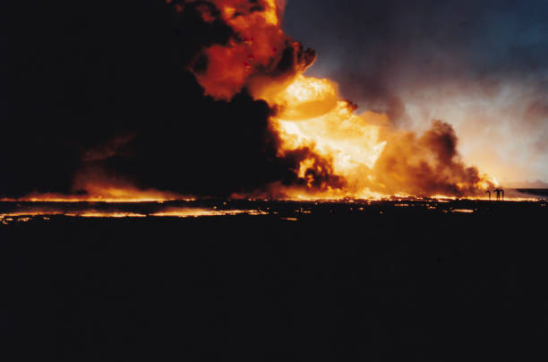 Massive oil well fire in field with oil slick, Kuwait stock photo