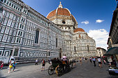A horse-drawn carriage passes through a plaza next to the majestic Florence Cathedral. Florence, Italy
