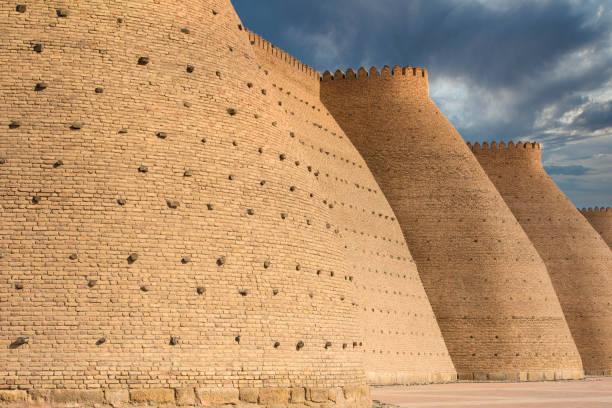 massieve muur van de ark, het fort van bukhara, oezbekistan - karavanserai stockfoto's en -beelden