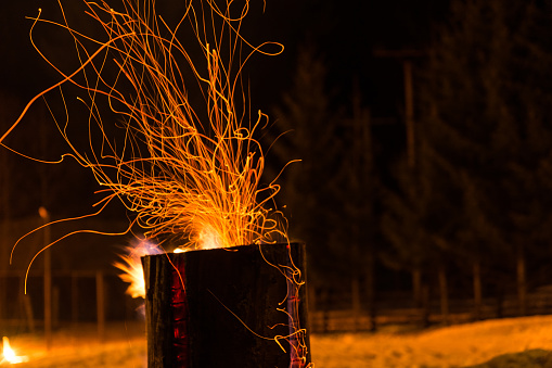 Massive wooden log on fire,  with sparks,  at fire camp in the mountains,  night time; outdoors