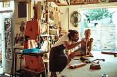 Close up of a father showing his daughter carpentry