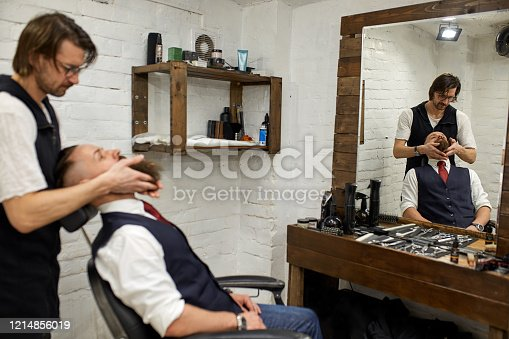 928445950 istock photo Master Barber does hairstyle and styling. Concept Barbershop. Beard styling and cut. styling of black beard. So trendy and stylish. Advertising and barber shop concept 1214856019