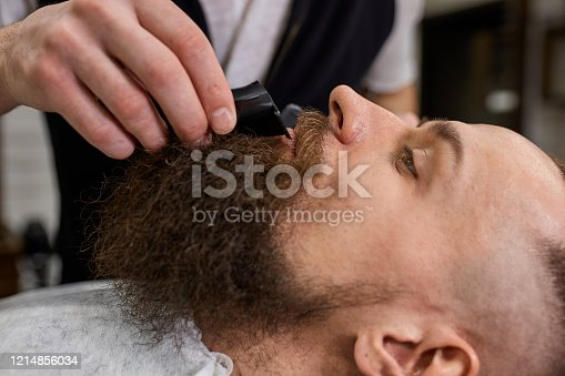 928445950 istock photo Master Barber does hairstyle and styling. Concept Barbershop. Beard styling and cut. styling of black beard. So trendy and stylish. Advertising and barber shop concept 1214856034