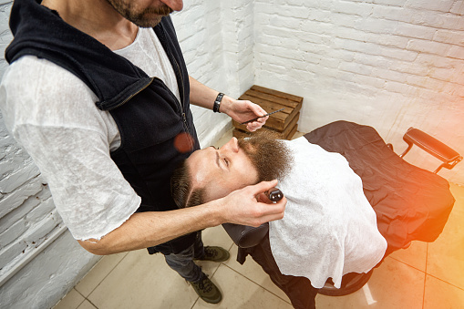 986804130 istock photo Master Barber does hairstyle and styling. Concept Barbershop. Beard styling and cut. styling of black beard. So trendy and stylish. Advertising and barber shop concept 1214856045