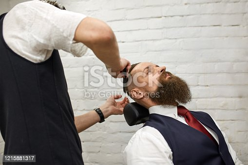 928445950 istock photo Master Barber does hairstyle and styling. Concept Barbershop. Beard styling and cut. styling of black beard. So trendy and stylish. Advertising and barber shop concept 1215881317
