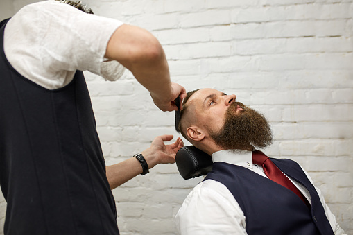 986804130 istock photo Master Barber does hairstyle and styling. Concept Barbershop. Beard styling and cut. styling of black beard. So trendy and stylish. Advertising and barber shop concept 1215881317