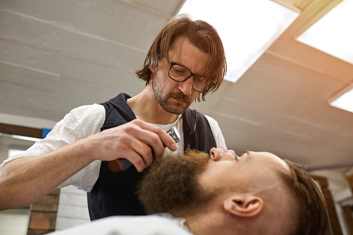 986804130 istock photo Master Barber does hairstyle and styling. Concept Barbershop. Beard styling and cut. styling of black beard. So trendy and stylish. Advertising and barber shop concept 1215881345
