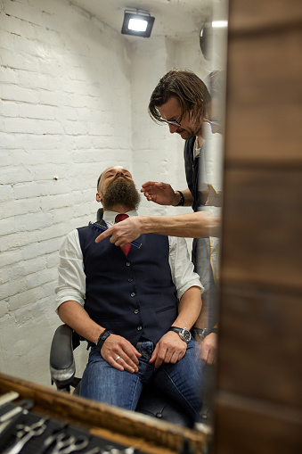 986804130 istock photo Master Barber does hairstyle and styling. Concept Barbershop. Beard styling and cut. styling of black beard. So trendy and stylish. Advertising and barber shop concept 1216740759