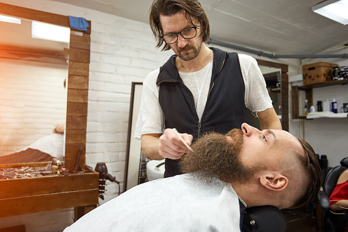 986804130 istock photo Master Barber does hairstyle and styling. Concept Barbershop. Beard styling and cut. styling of black beard. So trendy and stylish. Advertising and barber shop concept 1216740785