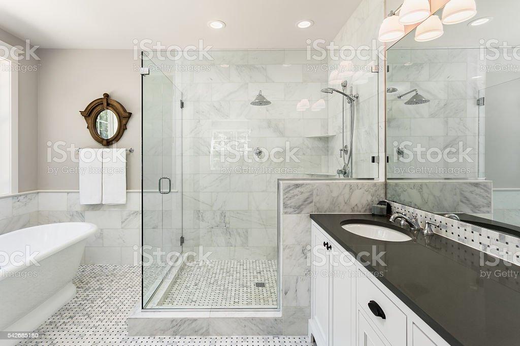 Master bathroom in new luxury home Beautiful master bathroom with shower, bathtub, and sink,  with high end furnishings, lights on Apartment Stock Photo