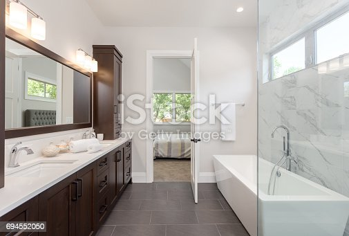 istock master bathroom interior in luxury home large mirror, shower, and bathtub. Includes dark hardwood cabinets and tile floor. View of bedroom 694552050