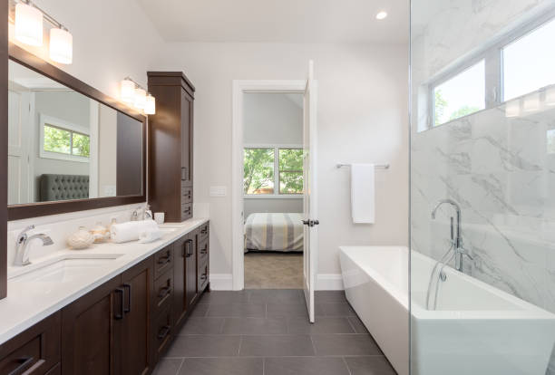master bathroom interior in luxury home large mirror, shower, and bathtub. Includes dark hardwood cabinets and tile floor. View of bedroom stock photo