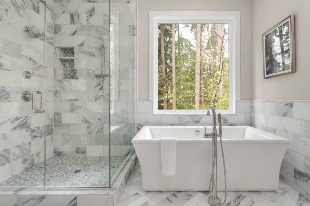 Master bathroom interior in luxury home with large shower with elegant tile and soaking bathtub. Includes large window with view of trees. stock photo