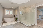 istock Master bathroom with freestanding tub and large all glass shower 1273548104