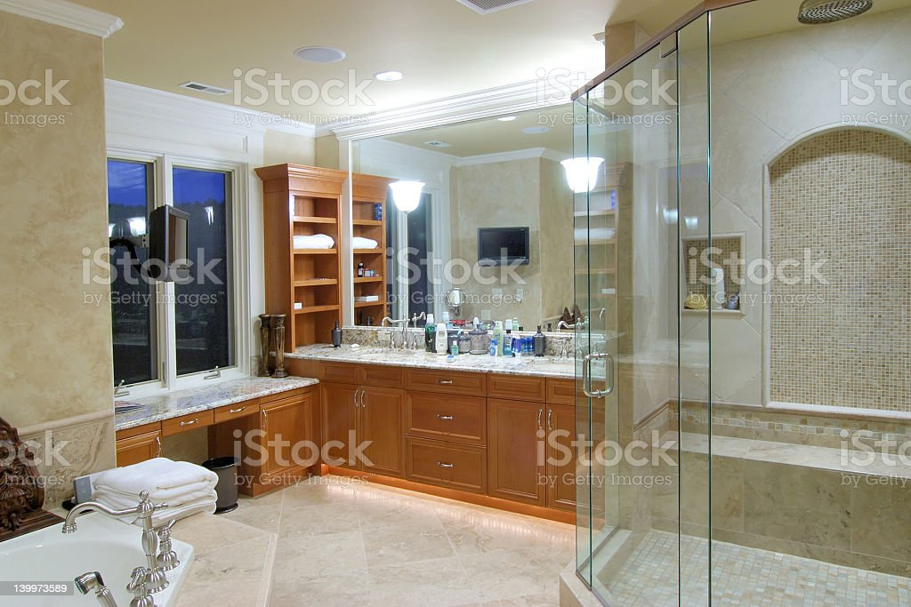 Master bathroom with glasses in shower, large tub and tile stock photo
