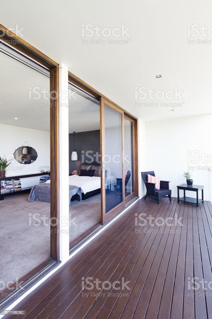 Master Bedroom And Large Glass Sliding Doors To Balcony Stock Photo