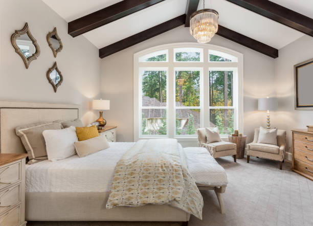 Master bedroom in new luxury home with chandelier and large bank of windows with view of trees stock photo