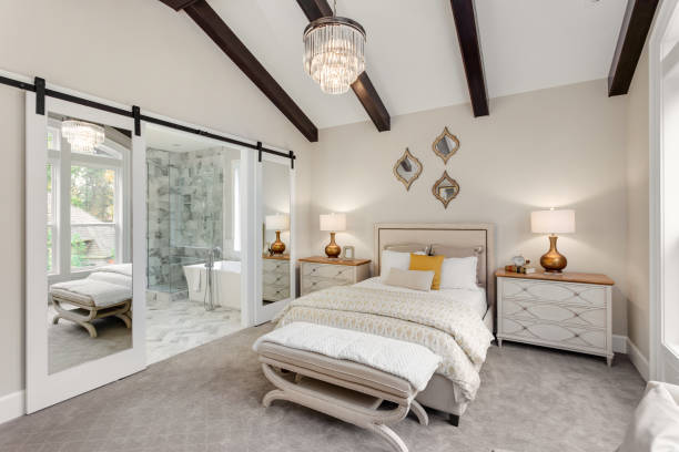 Master bedroom in new luxury home with chandelier and view of bathroom stock photo