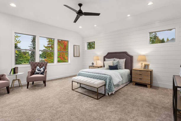 master bedroom in new luxury home with large windows, ceiling fan, carpet, and elegant decor. stock photo
