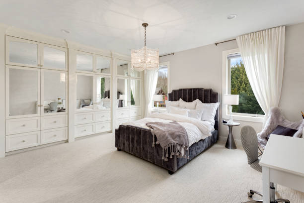 master bedroom in new luxury home with large windows, chandelier, carpet, and elegant decor. stock photo