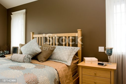Colorful bedding highlights the master bedroom of a new home.