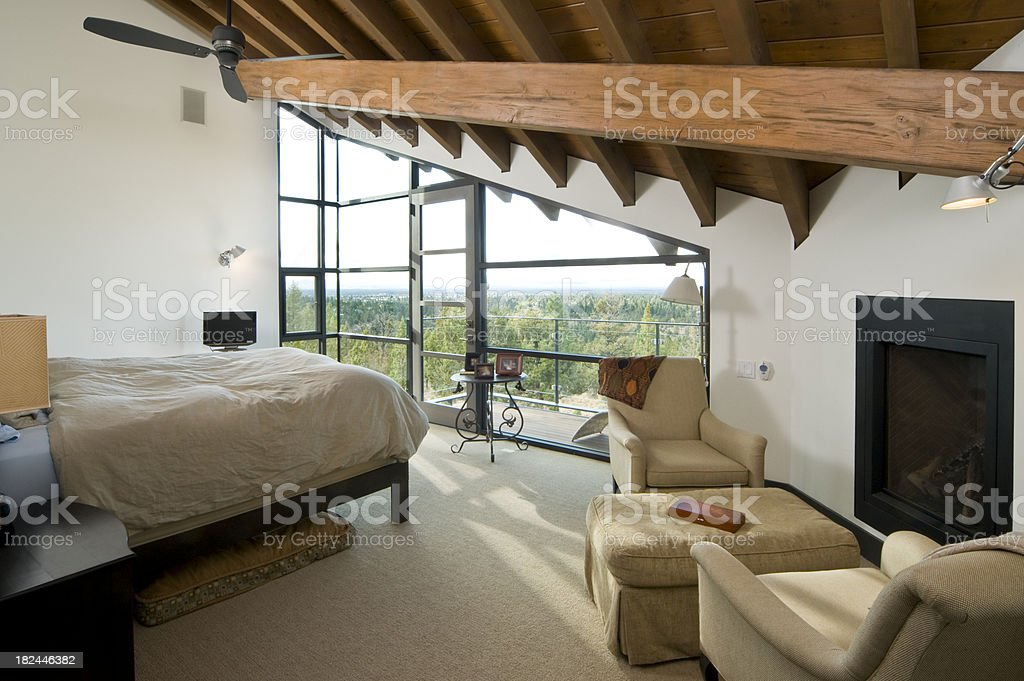 Master bedroom with high wooden beam stock photo