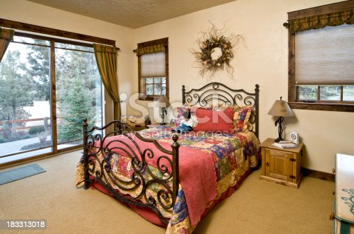 This stylish master bedroom has a beautiful wrought iron bed and colorful quilt.