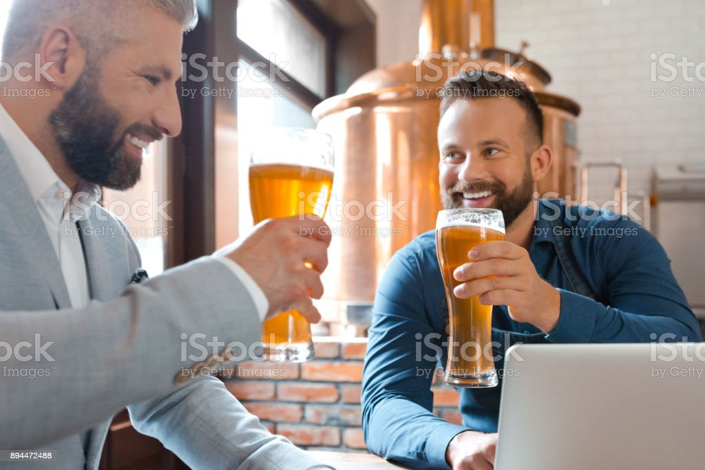 Master brewer and businessman having beers in brewery Master brewer and businessman having beers in brewery. Two men sitting at table with laptop and drinking beers at micro brewery. Adult Stock Photo