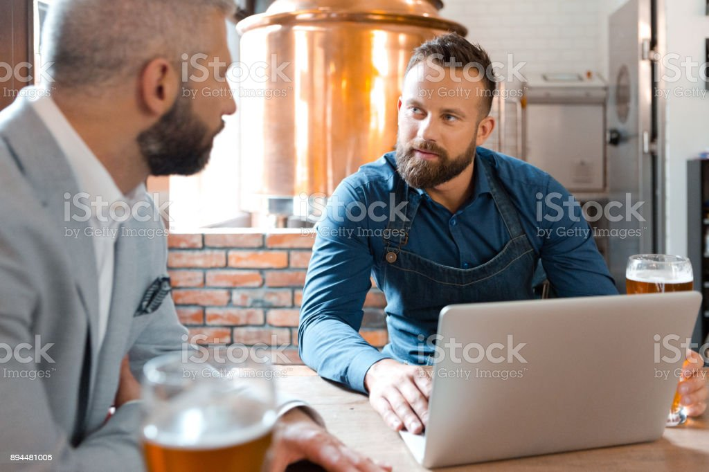 Master brewer meeting with businessman in brewery Master brewer meeting with businessman in brewery. Men sitting at table with laptop and beers at micro brewery. Adult Stock Photo