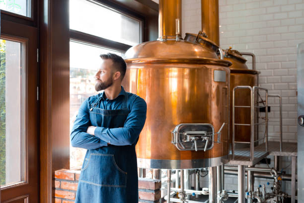 Master brewer standing in micro brewery stock photo