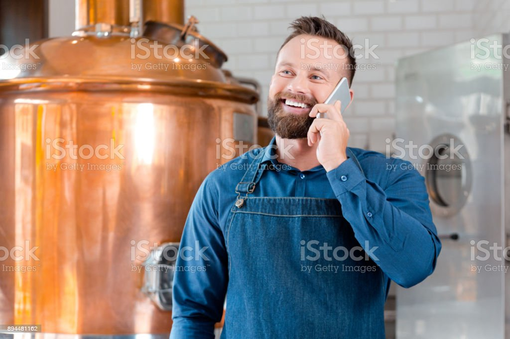 Master brewer talking on mobile phone in brewery Master brewer talking on mobile phone in fermenting section of beer manufacturing factory. Mature man talking on phone in his microbrewery Adult Stock Photo