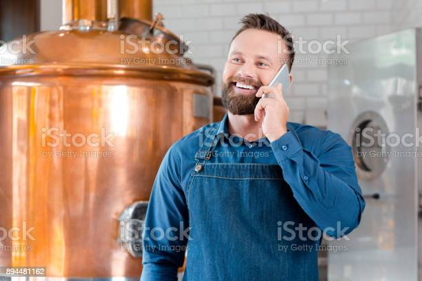 Master Brewer Talking On Mobile Phone In Brewery Stock Photo - Download Image Now