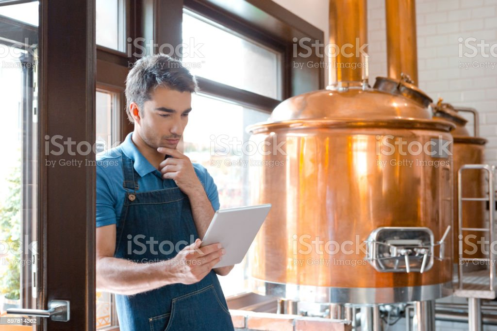Master brewer using a digital tablet in micro brewery Young male master brewer using a digital tablet in micro brewery. Bartender looking at digital tablet and thinking. Adult Stock Photo