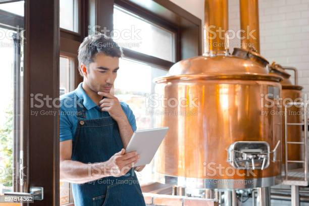 Master Brewer Using A Digital Tablet In Micro Brewery Stock Photo - Download Image Now