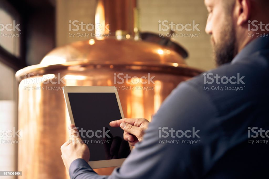 Master brewer using digital tablet at microbrewery Close up of male bartender using a digital tablet in micro brewery. Focus on master brewer hands using tablet pc. Adult Stock Photo