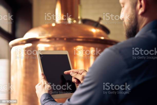 Master Brewer Using Digital Tablet At Microbrewery Stock Photo - Download Image Now