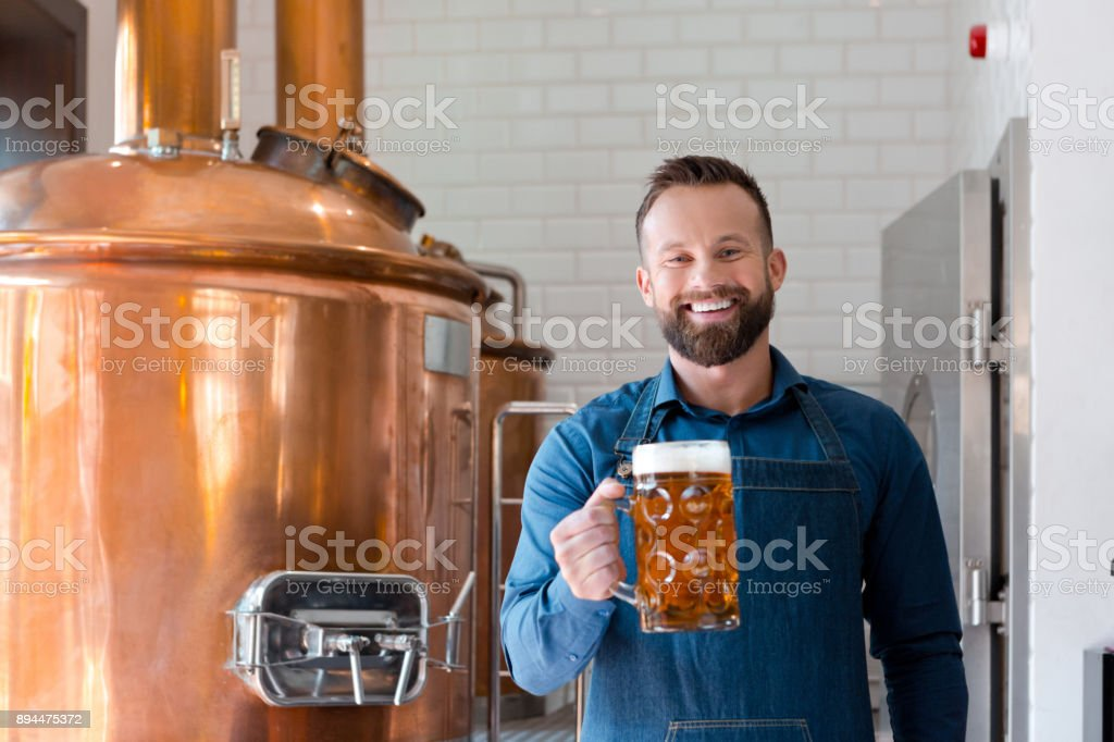 Master brewer with beer mug in microbrewery Mature man with a glass of beer at brewery plant. Brewer master working in alcohol manufacturing factory. Adult Stock Photo