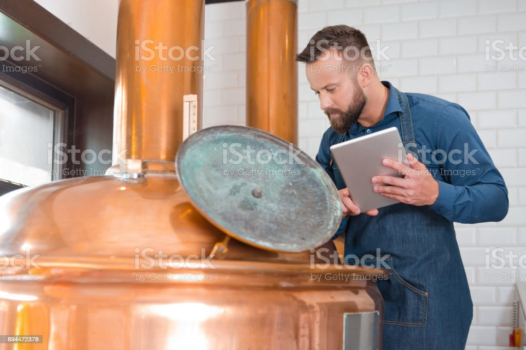Master brewer with digital tablet by a vat in brewery Mature man with digital tablet standing by a copper vat in brewery. Master brewer with a digital tablet in fermenting section of beer manufacturing factory. Adult Stock Photo