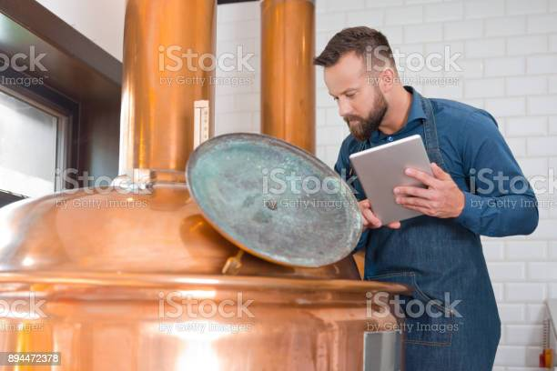 Master Brewer With Digital Tablet By A Vat In Brewery Stock Photo - Download Image Now