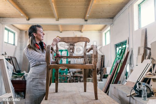 Renovation of old furniture - an old wooden armchair. Adult female carpenter in an apron in her workshop. Caucasian Woman sanding and preparing old and rustic chair. Professional carpenter sanding and refinishing wood surface.