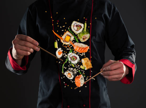 master chef holding chopsticks with flying sushi - sushi stock pictures, royalty-free photos & images