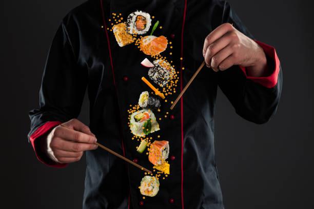 Meisterchef hält Stäbchen mit fliegendem Sushi – Foto