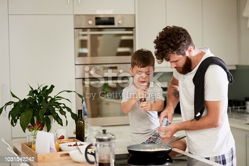 Shot of an adorable little boy and his father making breakfast together at home